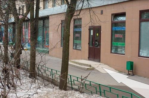 Справа от дороги - вход в здание через коричневые двери. На окнах стикеры - стеллажи, весы, тележки. Слева от дороги - зелёное ограждение.